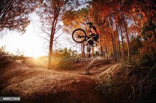 Exteme mountain biker dirt jumping and performing aerial maneuvers on a forest track
