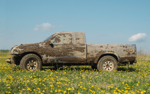 Extended cab truck covers in mud sitting in a meadow