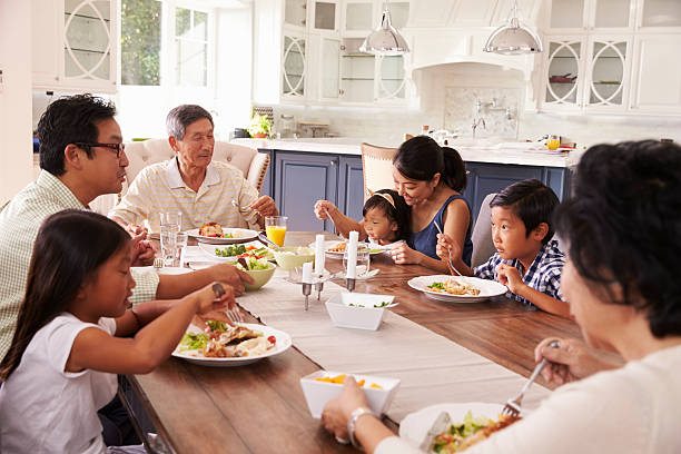 Extended Family Group Eating Meal At Home Together stock photo