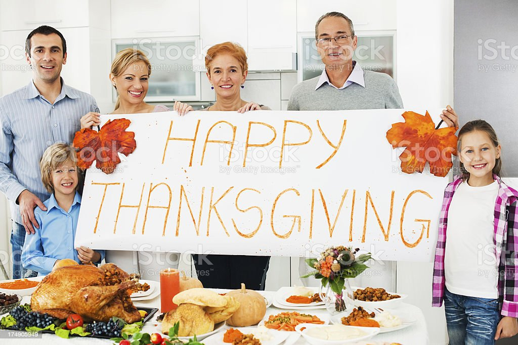 Extended family holding a big sign saying Happy Thanksgiving. royalty-free stock photo