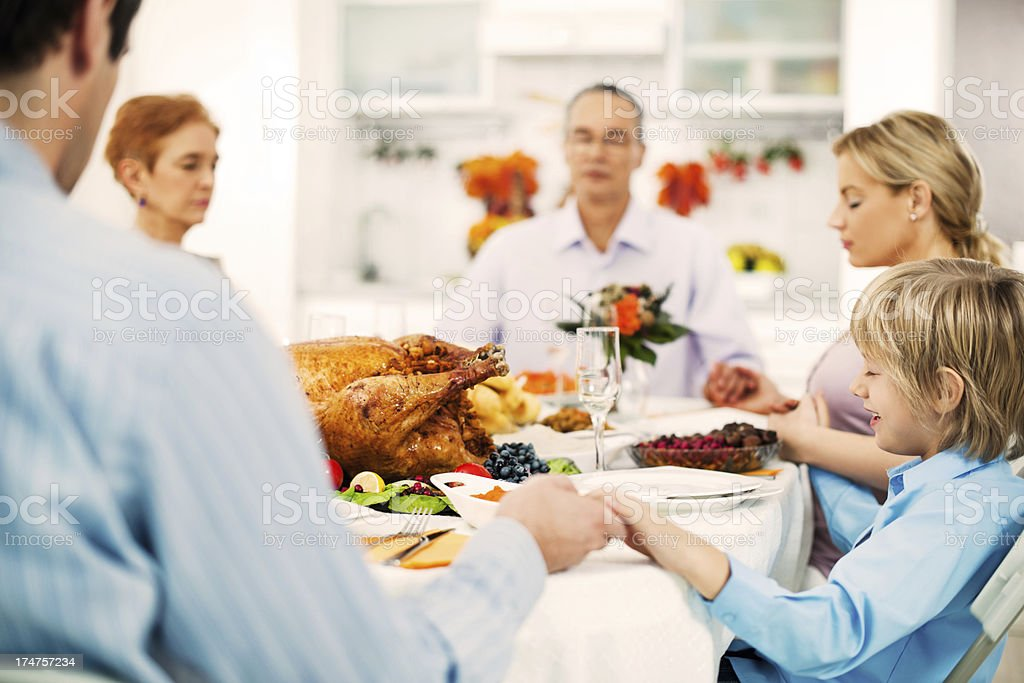Extended family holding hands and saying grace at Thanksgiving royalty-free stock photo