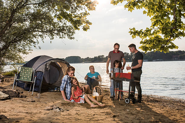 Extended family making barbecue during camping day by the river. stock photo