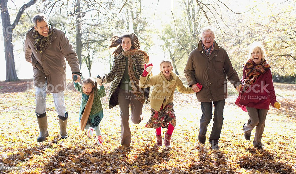Extended family running in park in autumn royalty free stockfoto
