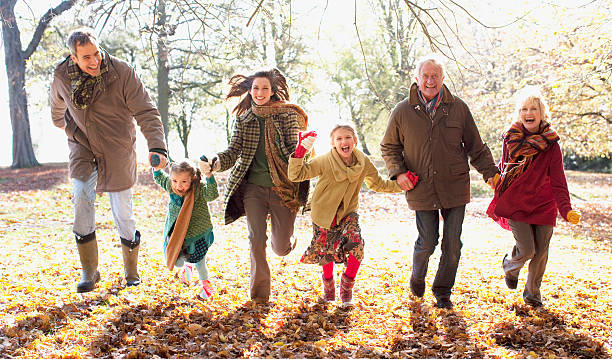 Extended family running in park in autumn stock photo