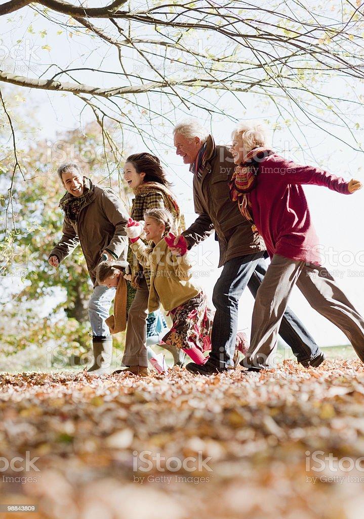 Extended family running in park stock photo