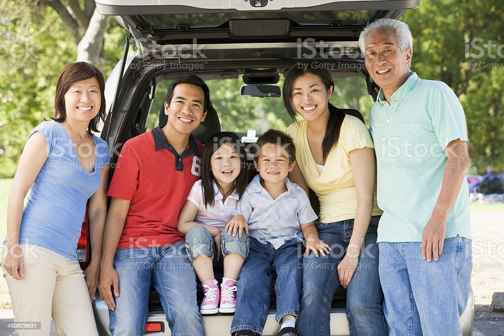 Extended family sitting in tailgate of car Extended family sitting in tailgate of car smiling to camera 20-29 Years Stock Photo