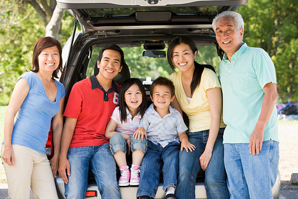 Extended family sitting in tailgate of car stock photo