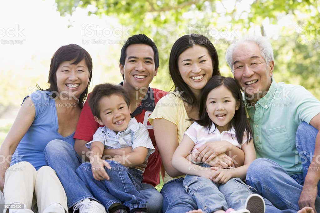 Extended family sitting outdoors smiling stock photo