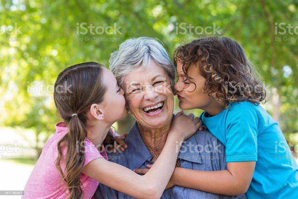 Familia sonriendo y beso en un parque - foto de stock