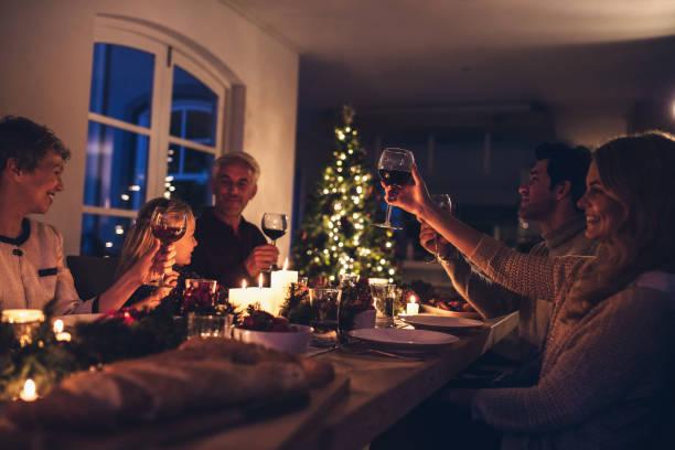 großfamilie toasten wein am weihnachtsessen - kinderzimmer tischleuchten stock-fotos und bilder