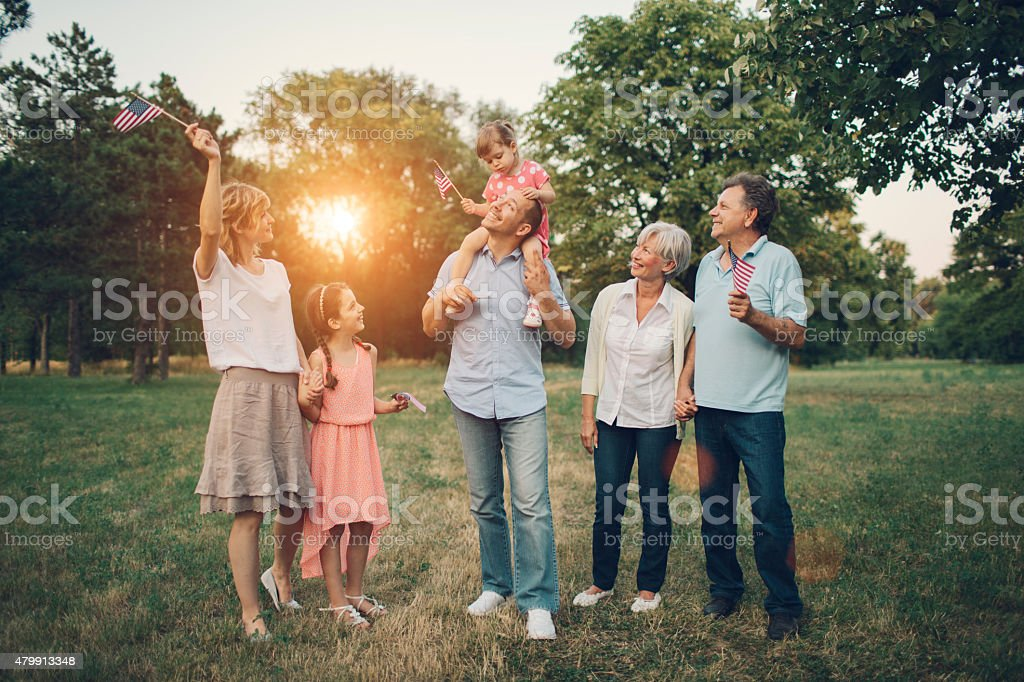 Extended Family Walking In A Park. stock photo