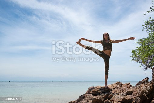 A young woman visiting Thailand does the Extended Hand to Big Toe Yoga Pose (Utthita hasta Padangusthasana) at a beach on Ko Phangan, Thailand