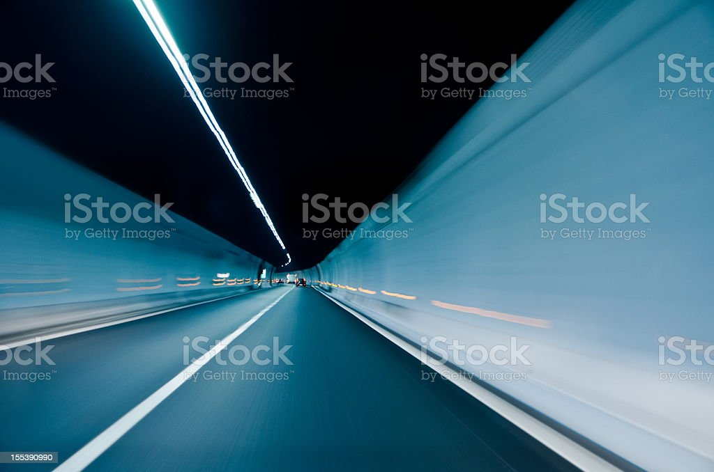 Extended long two-lane tunnel with white lighting stock photo