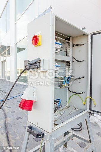 istock Extension cord is plugged in the socket of fuse box 607980898