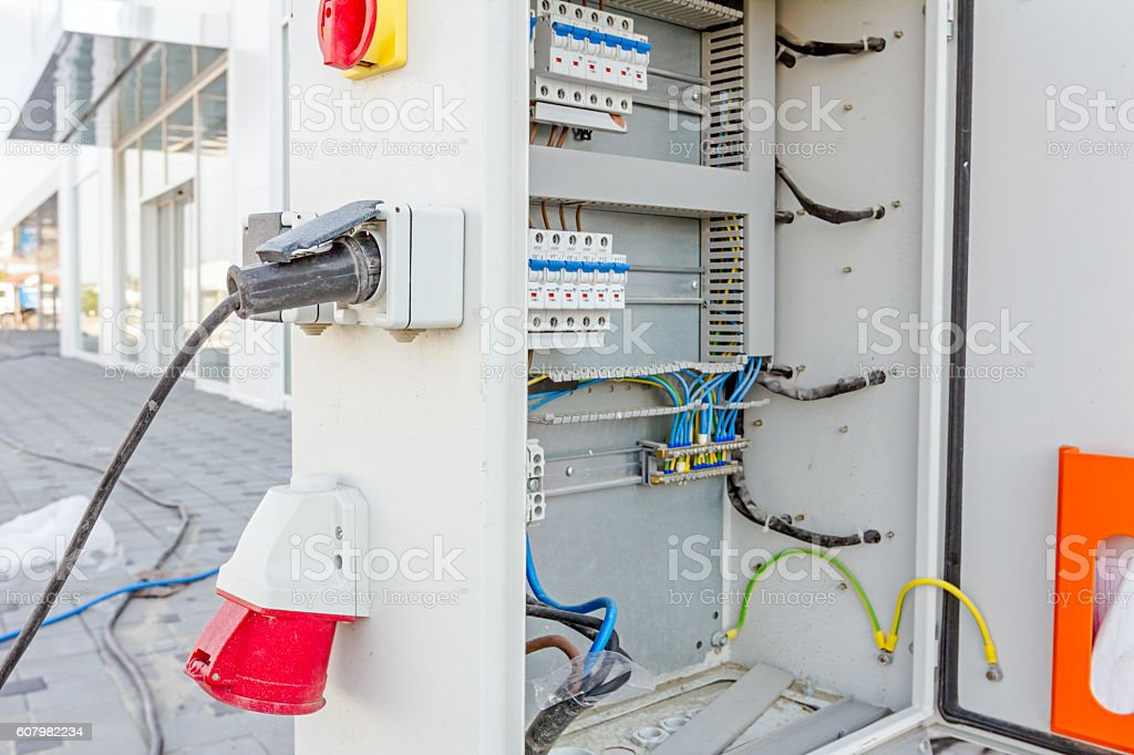 Extension cord is plugged in the socket of fuse box stock photo