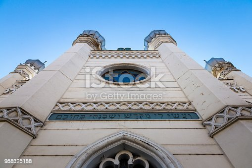 Building exterior of an old white synagogue in the city of CLuj Napoca, a city in the Transylvania region of Romania. The building has circular windows in which the blue Star of David can be seen, the popular Jewish symbol. Lots of room for copy space.