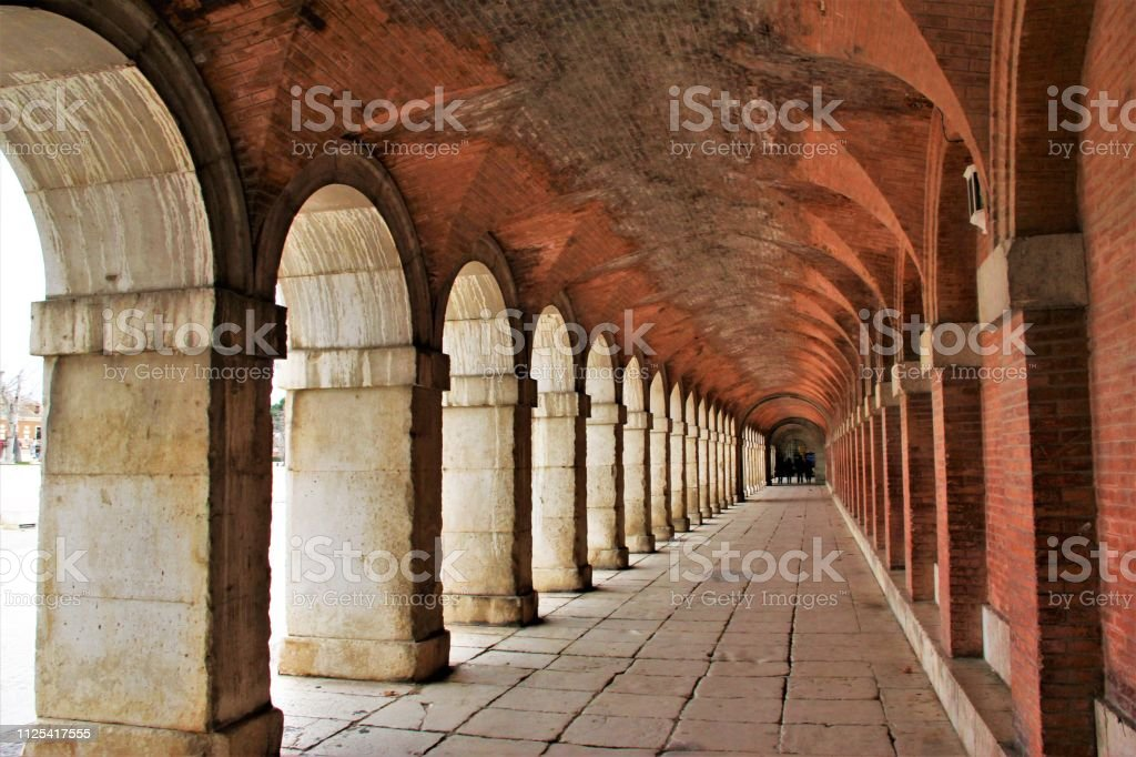 Exterior archway in Aranjuez, Madrid Old hallway made of stones and red bricks, sensation of never ending passage. Ancient Stock Photo