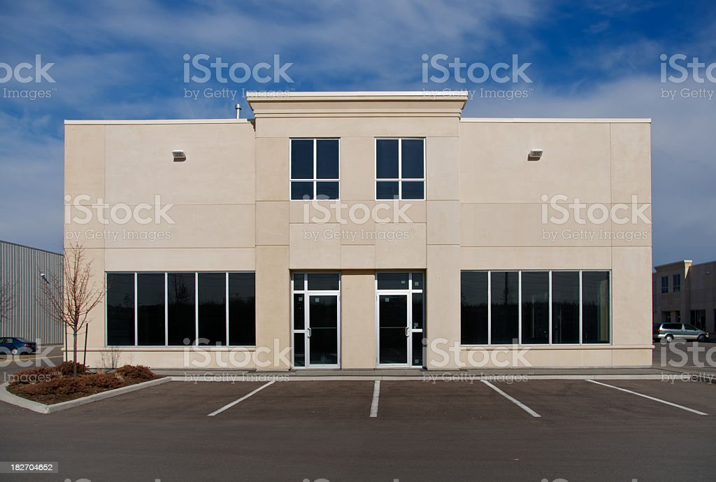 Exterior of a beige building with dark tinted windows royalty-free stock photo