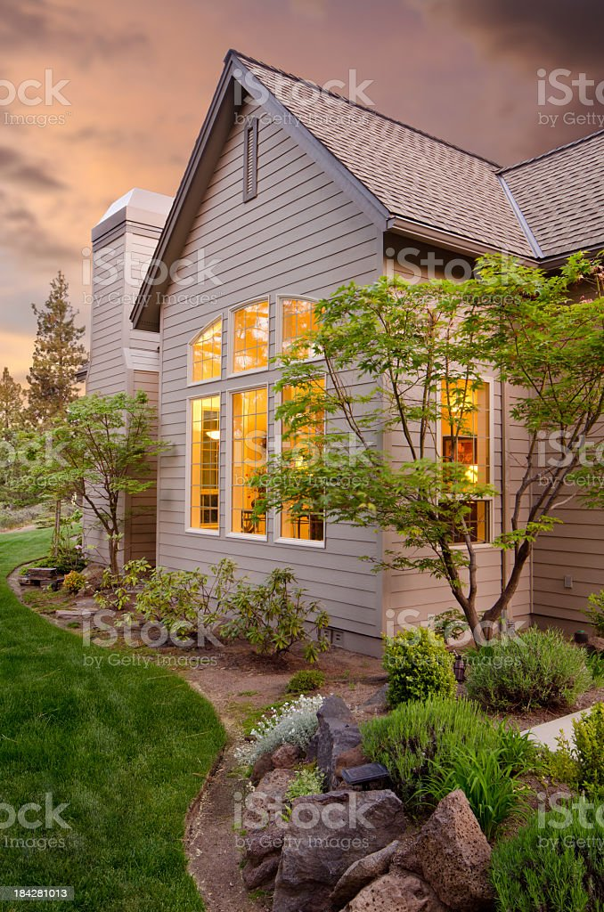 Exterior of a home with the lights on stock photo