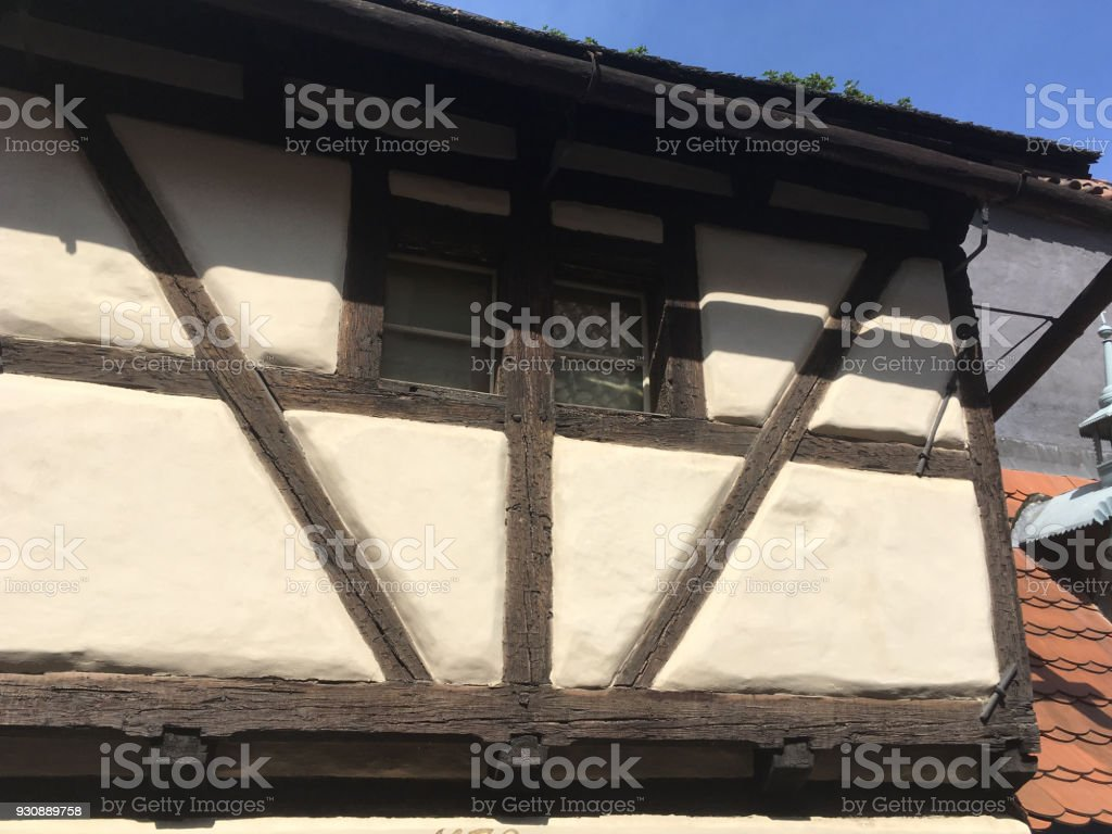 Exterior of a wood frame and stucco house similar to Tudor style with thatched roof in Prague, Czech Republic. Medieval vernacular house with wood frame and supports. stock photo