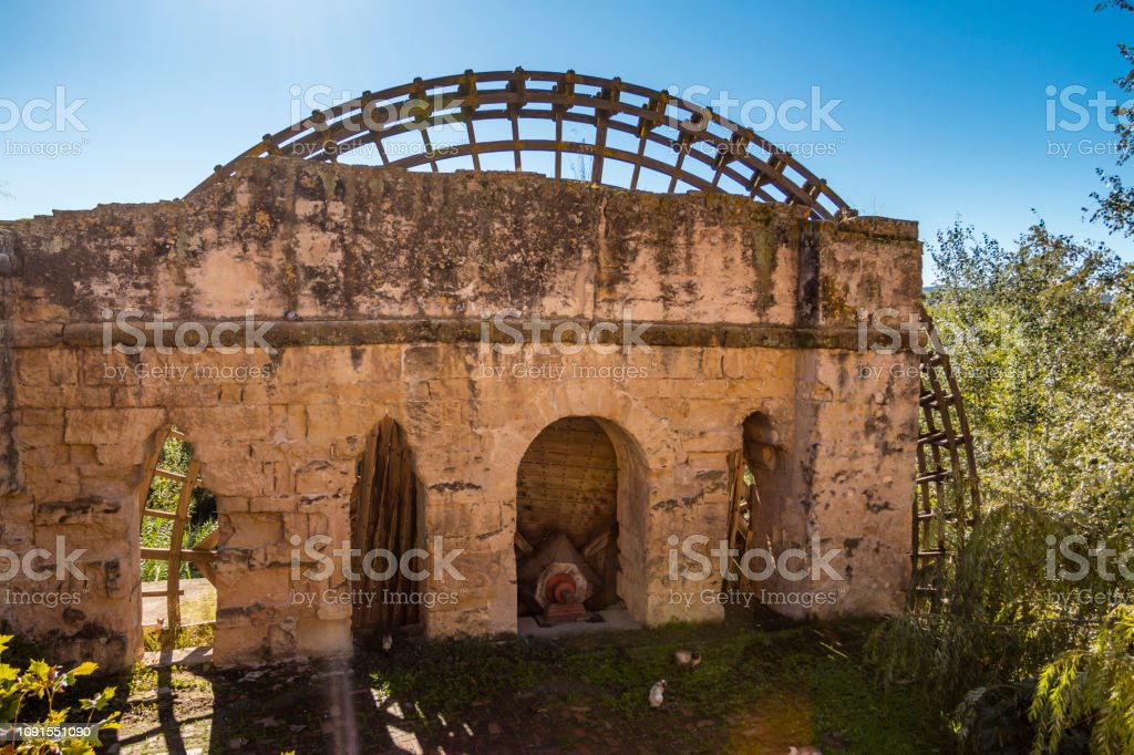 Ancient stone mill with wooden wheel in overgrown field in sunlight...