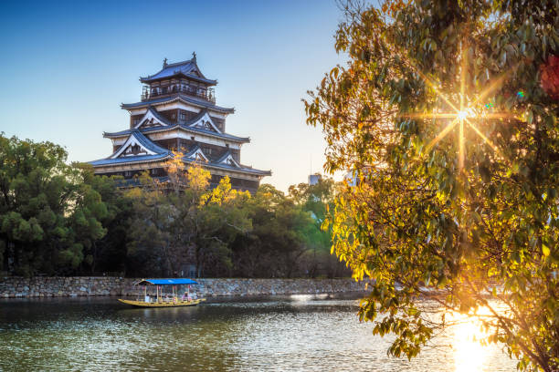 exterior of Hiroshima castle with tourists boat at sunset. Japan 24 maech 2019, Hiroshima - Japan: Hirishima Castle with a boat with tourists in front at sunset hiroshima prefecture stock pictures, royalty-free photos & images