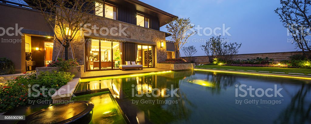 exterior of modern building near pond at twilight stock photo