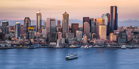 View of crowded modern cityscape with 1201 Third Avenue, U.S. Bank Centre, ship moving in foreground, Seattle, Washington, United States.