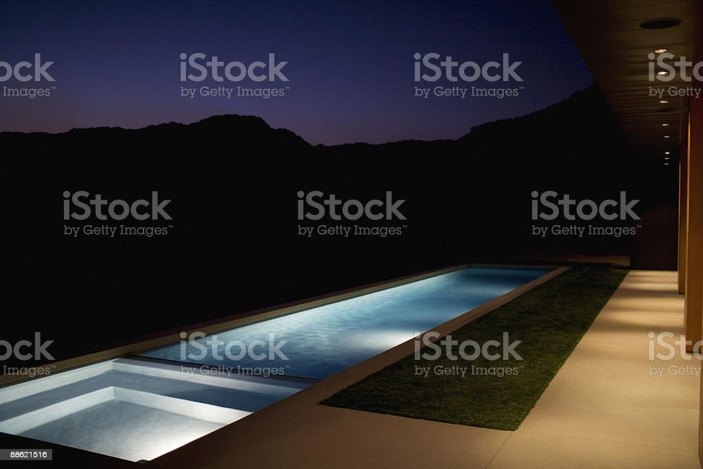 Exterior of modern house and swimming pool at night stock photo