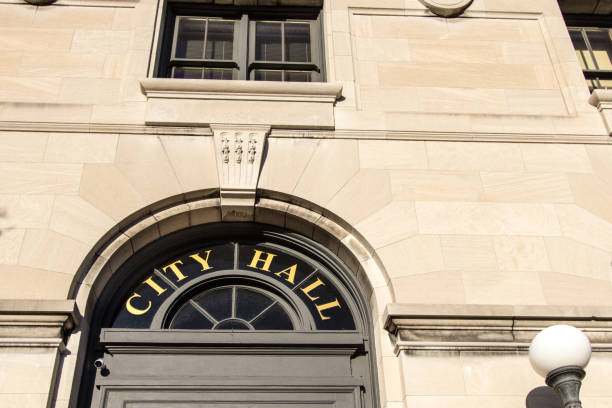 Exterior Of Municipal City Hall Sign In Window City Hall Sign. Front entrance to city hall building. This is a public owned building and not a private property or residence. town hall stock pictures, royalty-free photos & images