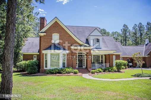 Front view entrance of Exterior of Red Brick Traditional Southern Home. large Red Brick Traditional House Home on a wooded lot in the south