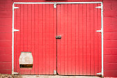 Red barn door with small animal door entry