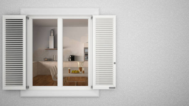 Exterior plaster wall with white window with shutters, showing interior modern kitchen with table, blank background with copy space, architecture design concept stock photo