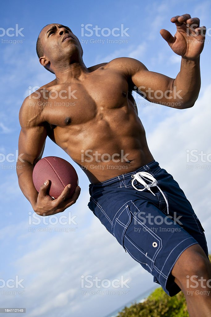 exterior shot of African-american male running with football royalty-free stock photo