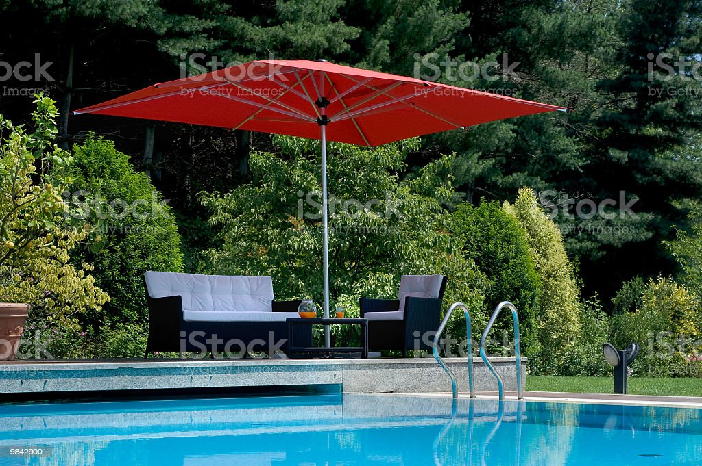 Exterior swimming-pool and relax area with parasol, surrounded by nature royalty-free stock photo