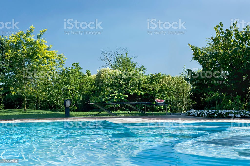 Exterior swimming-pool surrounded by trees and beautiful green park royalty-free stock photo