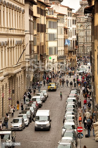 Florence, Italy, June 3, 2019: Exterior view from an elevated vantage point along a street in the centre of Florence with many parked cars and pedestrians