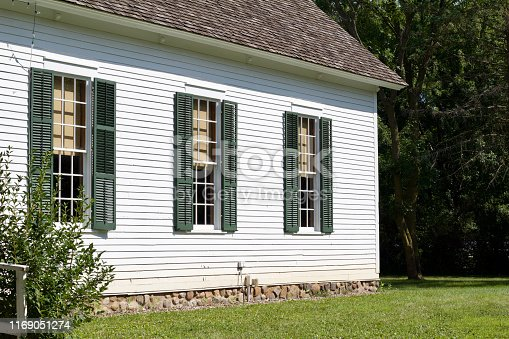 istock Exterior view of a 19th Century midwestern USA one room schoolhouse building with bell tower 1169051274