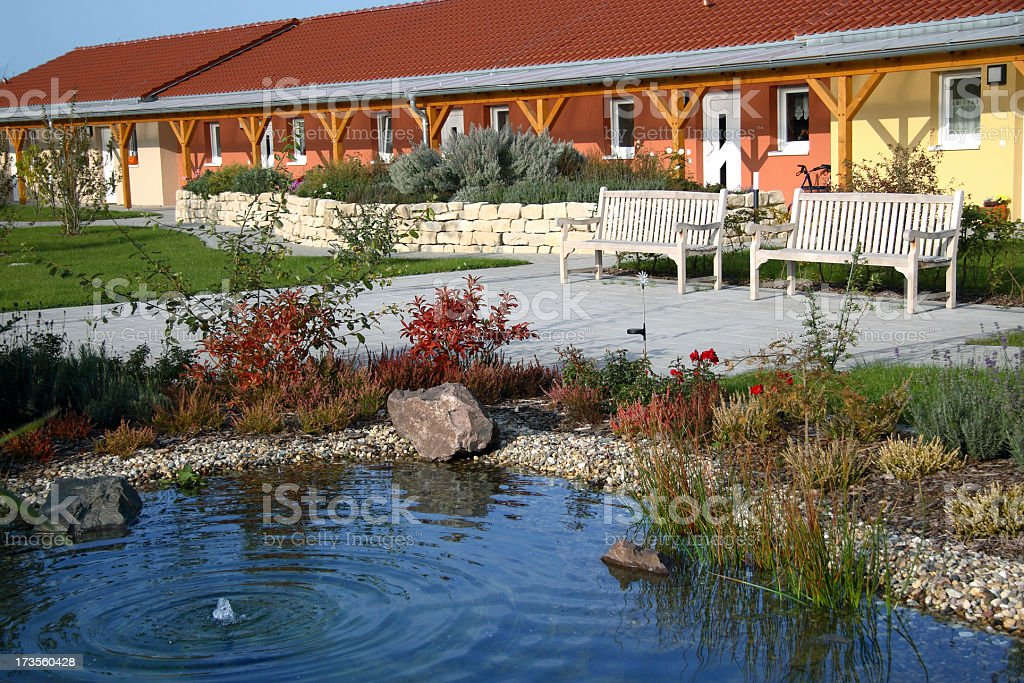 Exterior view of a modern Nursing Home overlooking pond stock photo
