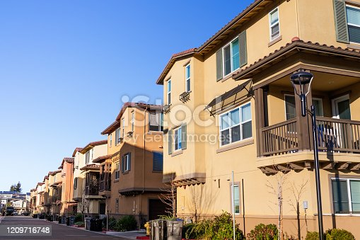 108220043 istock photo Exterior view of a row of identical townhouses; Sunnyvale, San Francisco bay area, California 1209716748