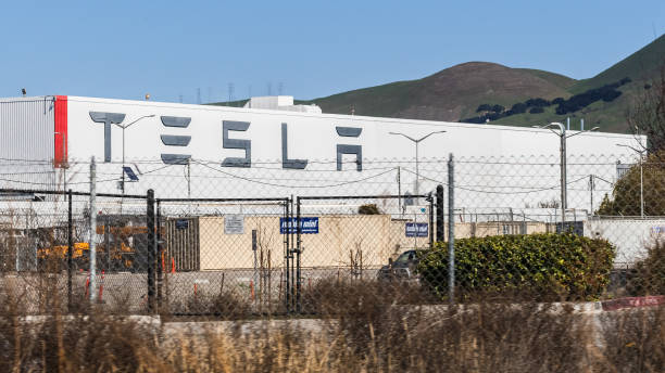 Exterior view of Tesla Factory located in East San Francisco bay area Feb 17, 2020 Fremont / CA / USA - Exterior view of Tesla Factory located in East San Francisco bay area; Large Tesla logo displayed on one of the buildings visible behind a fence tesla motors stock pictures, royalty-free photos & images