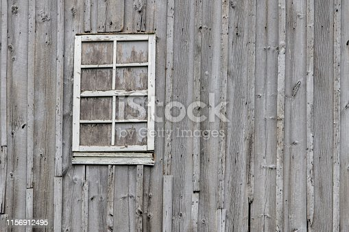 Exterior wall and window of a traditional weathered  wood barn in the American Midwest