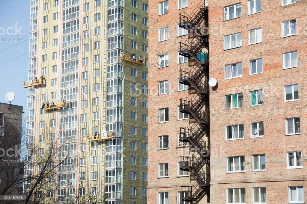 Exterior Work on Unfinished Apartment Block. Builders on gondolas...