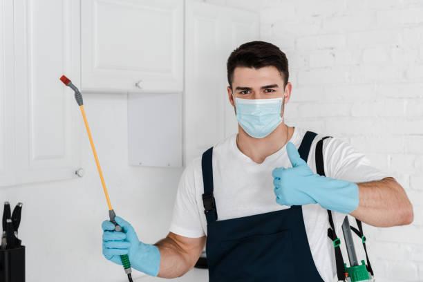 sterminatore in uniforme tenendo spray tossico e mostrando pollice in su - attrezzatura per la disinfestazione foto e immagini stock