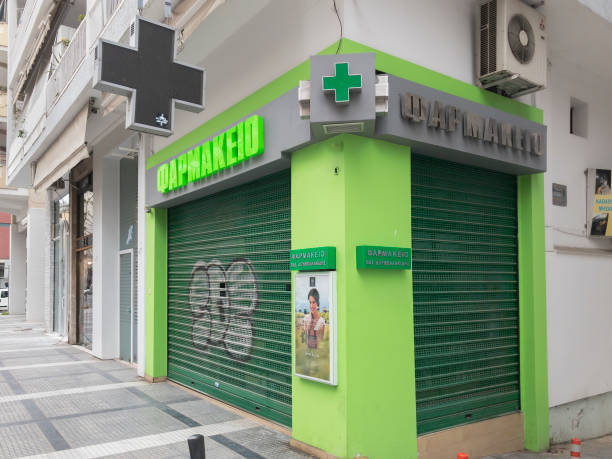 External day view of Hellenic shop with illuminated green cross and security shutter gate. stock photo