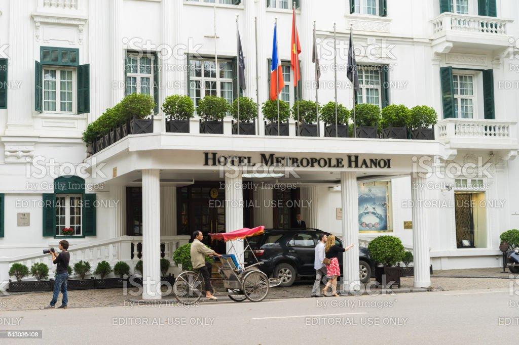 Hanoi, Vietnam - Mar 15, 2015: External front view of Hotel Sofitel Legend Metropole Hanoi with running cyclo. Sofitel Legend Metropole Hanoi is a well-known French architecture in Vietnam stock photo