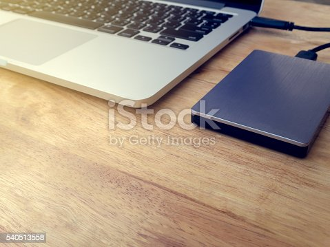 External or portable hard drive (HDD) connected to laptop computer for transfer or backup data on wooden texture office desktop with copy space