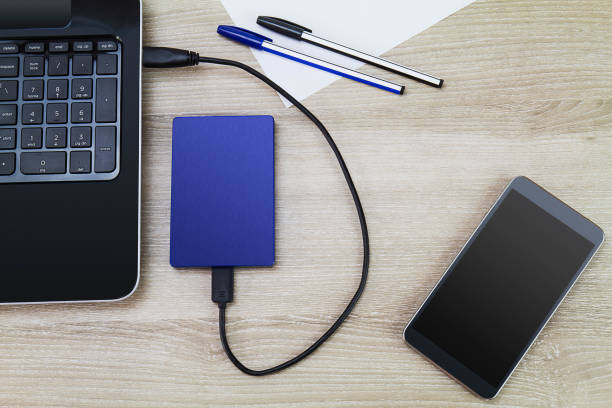 External hard drive connecting to laptop with smartphone, pens and paper on wooden desk, business concept External hard drive connecting to laptop with smartphone, pens and paper on wooden desk, business concept external hard disk drive stock pictures, royalty-free photos & images