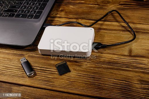 External HDD connected to laptop computer, SD memory card and USB flash drive on a wooden desk. Concept of data storage