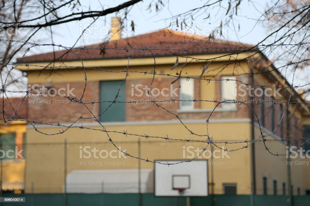 external view of a reformatory with a basketball court and barbed wire stock photo